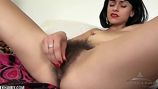 Andy Moon plays with her hairy pussy in catsuit